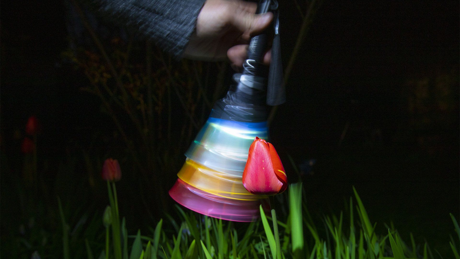 A hand waves a torch with colourful cups taped to the end, causing it to blur.
